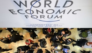 Participants at the World Economic Forum (WEF) annual meeting chat under a sign on January 25, 2012 at the Congress Center in Davos. The world's political and business elite will shelter from
