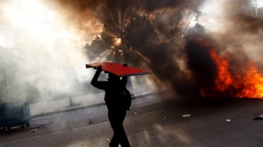 MADRID, SPAIN - MARCH 26:A protester carries a wooden table as he walks next to a burning barricade during a protest against the government's education reforms and cutbacks in university gran