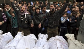 Syrians shout slogans as they gather around the shrouded bodies of civilians, who were executed and dumped in the Quweiq river, during their funeral outside the Yarmuk school in the Bustan al