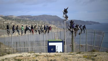 MELILLA, SPAIN - APRIL 03:African migrants attempt to scale the fence at the border between Morocco and the North African Spanish enclave of Melilla, on April 3, 2014, in Melilla, Spain. Roug