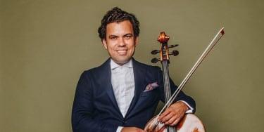 Musician Francesco Vila posing in a suit with his cello.