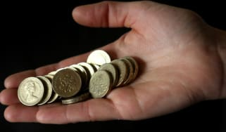 A person holds one pound coins