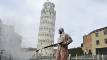 Health workers disinfect the area around the Tower of Pisa