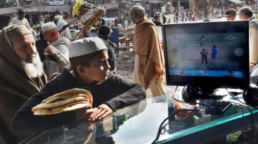 Afghans refugees watch the live broadcast of the Cricket World Cup match between Afghanistan and Bangladesh at a market in Peshawar on February 18, 2015. Born in refugee camps and nurtured in