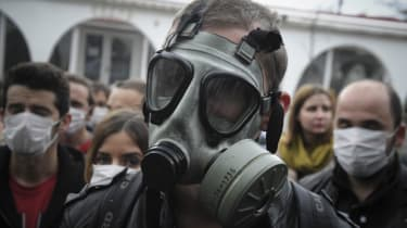 An Albania wearing a gas mask in protest of a plan to dispose of Syria's chemical weapons in Albania