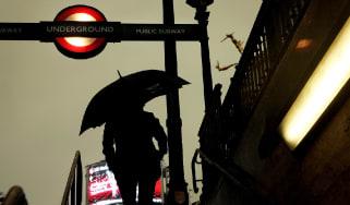 Man holds umbrella outside London Underground station