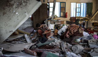 A Palestinian collects human remains from a Gaza school