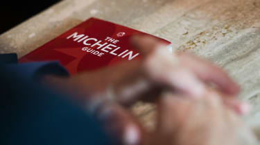 Michael Ellis from Michelin poses with the Michelin guide book at a restaurant in Washington, DC on October 12, 2016. The Michelin Guide unveiled its first edition for the US capital Washingt