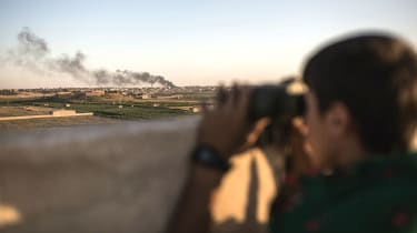 Kurdish fighters look on as their fellow soldiers clash with IS near Hasekeh, Syria