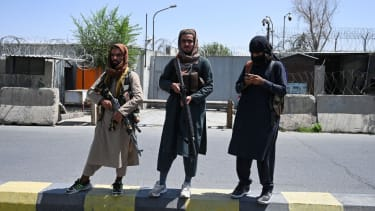 Taliban fighters stand guard along a street in Kabul