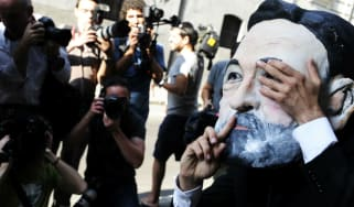 A protester wearing a mask depicting Spanish PM Mariano Rajoy outside Spain's national court