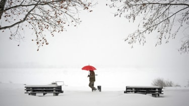 A man walks through snow covered banks of the Danube river in Zemun near Belgrade on February 12, 2012. Cold weather claimed seven more lives on Sunday in the Balkans -- two in Albania, one i
