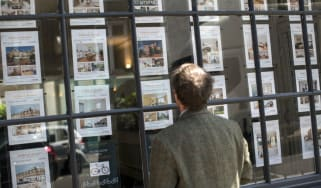 A potential home buyer looks at properties displayed in an estate agent window