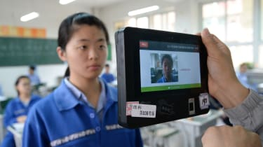 A teacher uses a machine which employs both fingerprint and facial recognition technology to check the identification of a student before a simulated college entrance exam in Handan in China'