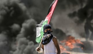 A Palestinian boy holds his national flag during clashes with Israeli security forces near the Gaza border