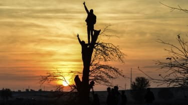 Kurdish people make the V sign while standing on a tree as they rally near the border with Syria in Sanliurfa on November 30, 2014. Turkey's main pro-Kurdish party on Sunday pressed Prime Min