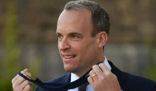 Dominic Raab removes his protective face mask.