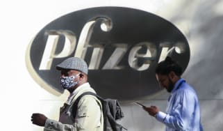 A man in a face mask walks past the Pfizer headquarters in New York