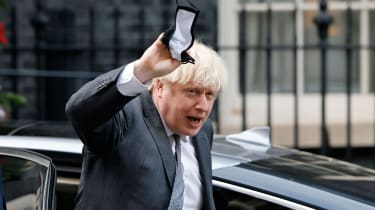 Boris Johnson gestures to members of the media as he arrives back at 10 Downing Street