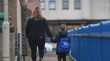 A woman walks child to school