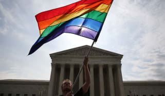 WASHINGTON, DC - JUNE 25: A gay marriage waves a flag in front of the Supreme Court Building June 25, 2015 in Washington, DC. The high court is expected rule in the next few days on whether s