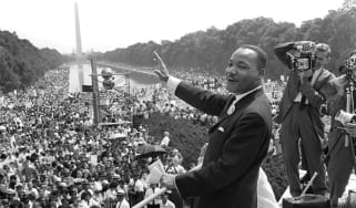 Martin Luther KIng waves to supporters from the steps of the Lincoln Memorial