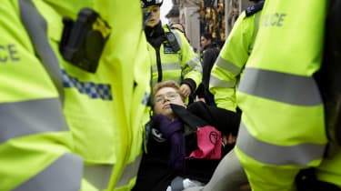 An Extinction Rebellion demonstrator is carried away by a police officers