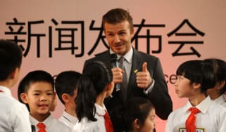 Football superstar David Beckham (C) answers questions from a group of pupils during a press conference at a primary school in Beijing on March 20.Beckham flew to Beijing on March 20 to take