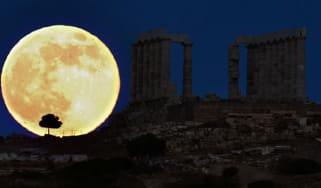 A supermoon rises behind a Greek temple